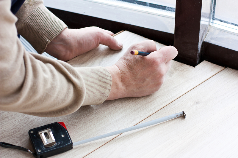 Worker makes markup for laying laminate flooring