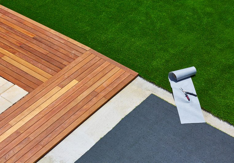 Artificial grass installation in deck garden with tools
